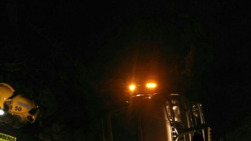 Dos bomberos junto al vehículo accidentado en la tarde del domingo en Barlovento. Foto: BOMBEROS LA PALMA.