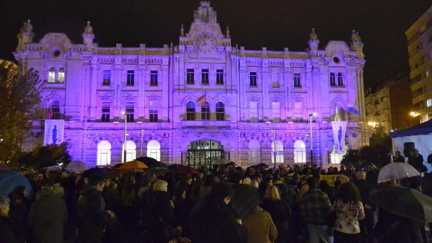 Concentración contra la violencia de género con el Ayuntamiento de Santander, al fondo iluminado con el color violeta, símbolo de esta lucha. | RUBÉN VIVAR