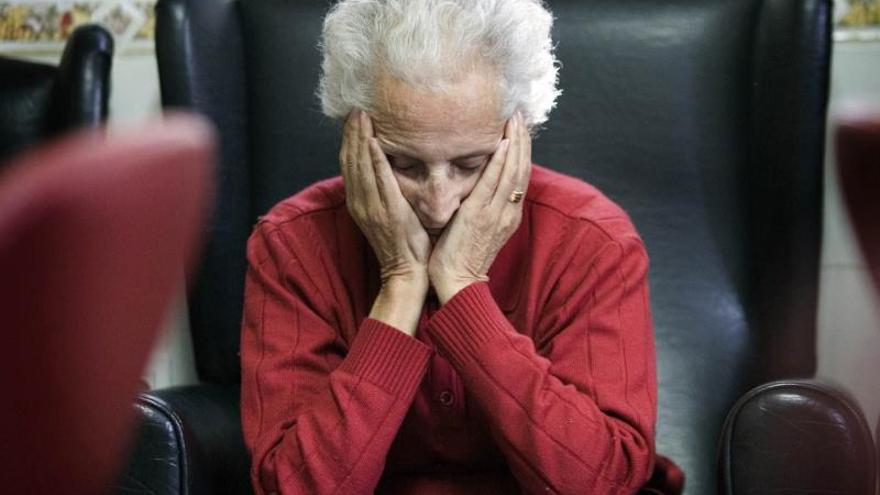 Una enferma de alzheimer descansa en la sala de estar de un centro de día.