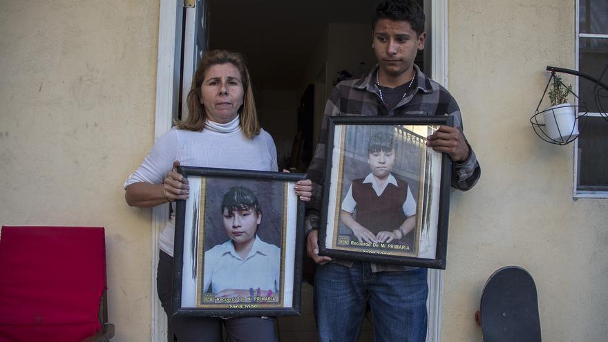 Gladis y uno de sus chicos posan con las únicas fotos que tienen de sus hijas desaparecidas