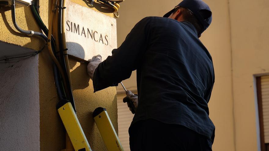 Un operario retira la placa de una calle que incumple la Ley de Memoria Histórica.