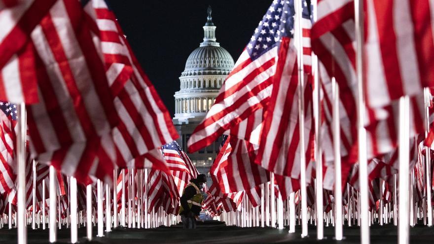 Una persona pasa entre las 200.000 banderas instaladas frente al Capitolio para la investidura de Biden. EFE/JUSTIN LANE