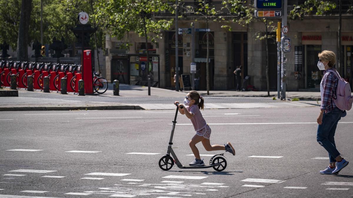 Una niña juega con un patinete en Barcelona el pasado 26 de abril de 2020, cuando España permitió los paseos de menores durante el confinamiento