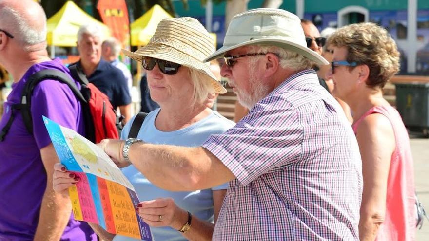 Turistas de visita en Canarias echan un vistazo a un mapa