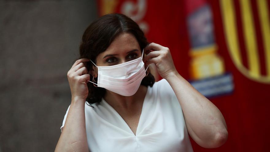 La presidenta de la Comunidad de Madrid, Isabel Díaz Ayuso se coloca una mascarilla durante una rueda de prensa.