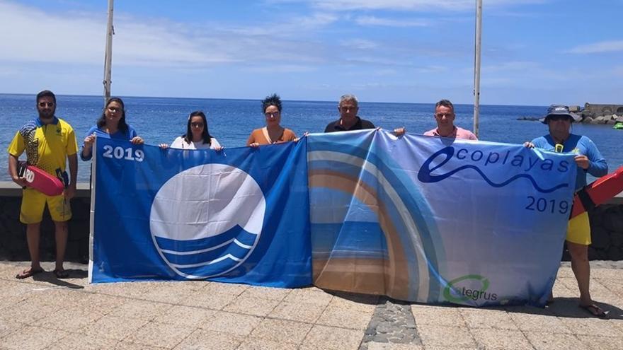 Las autoridades municipales y los socorristas muestran las banderas.