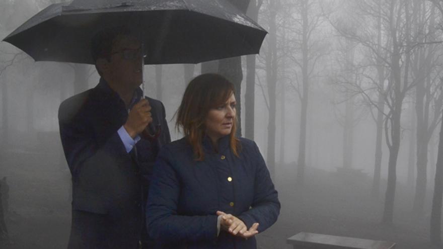 El vicepresidente del Gobierno, Pablo Rodriguez, sostiene el paraguas en el que se refugia junto a la consejera de Política Territorial y Medio Ambiente, Nieves Lady Barreto