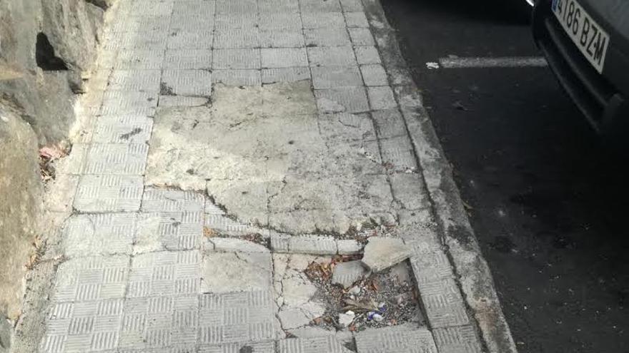 En la imagen, una acera con el pavimento deteriorado.