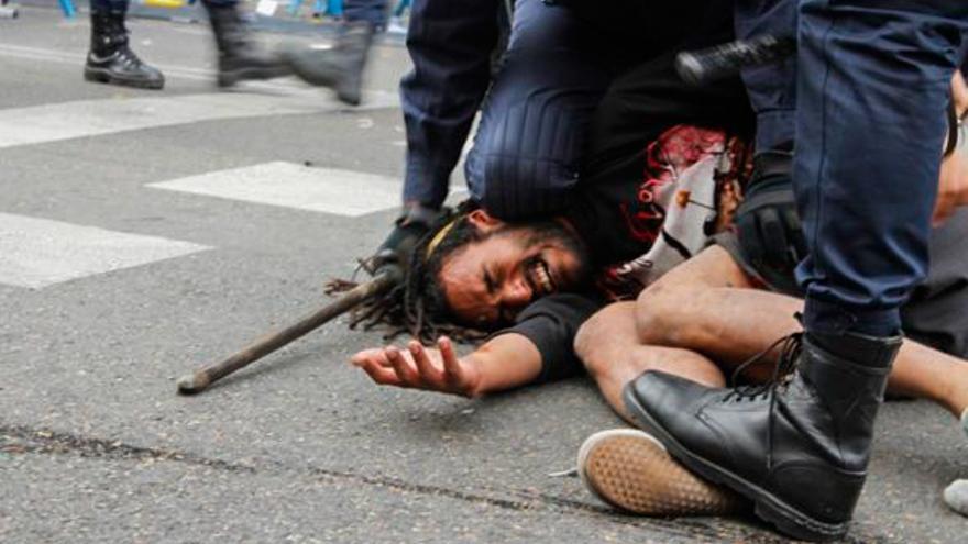 Policías antidisturbios aplastan a un manifestante el 25S. Foto: Fotogracción
