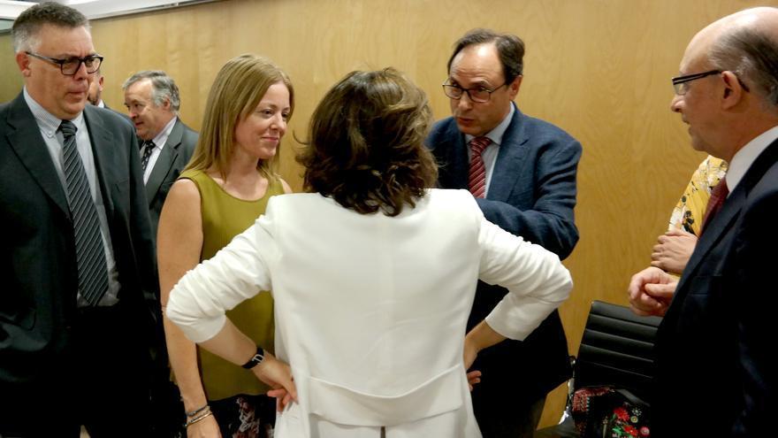 El conseller Vicent Soler dialoga con la vicepresidenta Soraya Sáenz de Santamaría en presencia del ministro Cristóbal Montoro y la secretaria autonómica Clara Ferrando