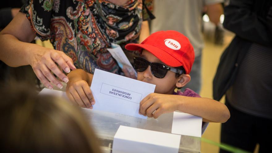 Un niño deposita el voto de su madre en la urna. / Enric Català