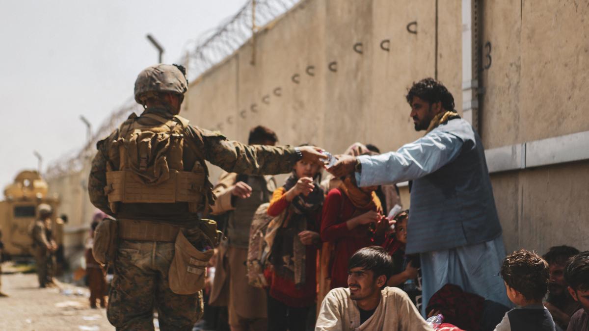 Un 'marine' de EEUU distribuye agua a los evacuados en el aeropuerto de Kabul.