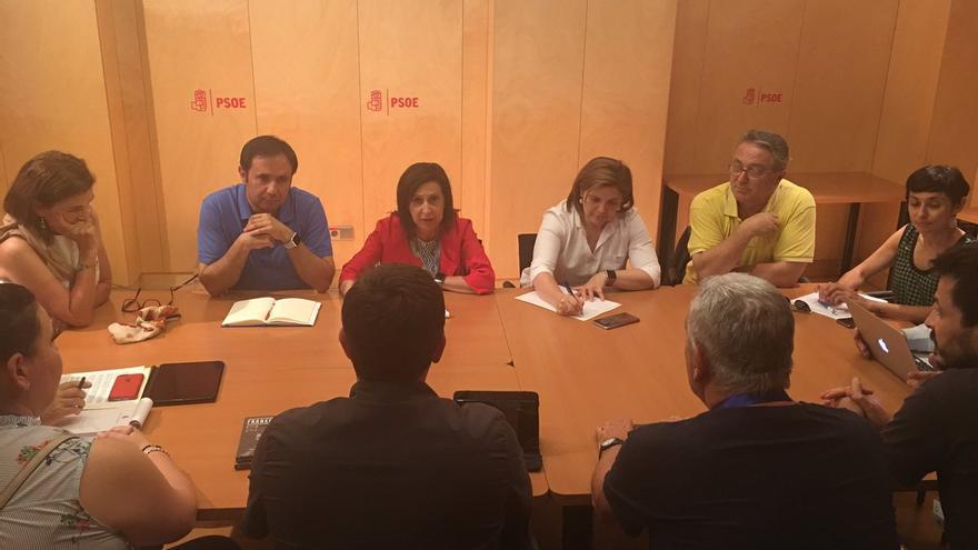 La portavoz parlamentaria del PSOE, Margarita Robles, de rojo, junto a otros diputados socialistas frente a víctimas del Alvia