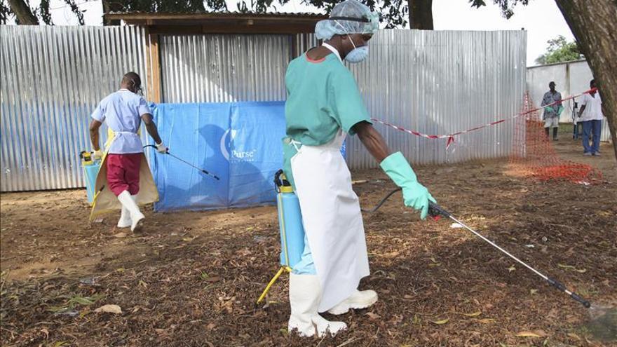 Enfermeros liberianas esparcen desinfectante como la prevención contra el virus ébola, fuera de la sala de espera de la unidad de aislamiento ELWA en Monrovia, Liberia, en agosto de 2014.