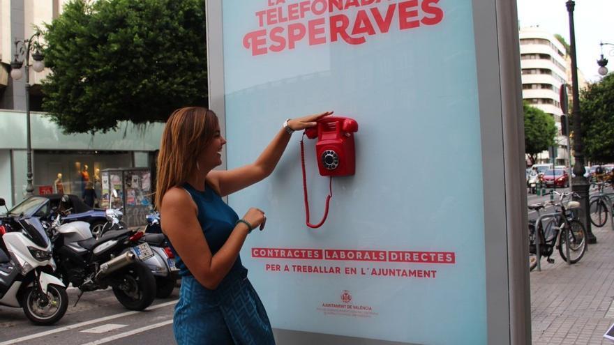 La portavoz municipal del PSPV, Sandra Gómez, junto al teléfono informativo instalado en la calle Colón