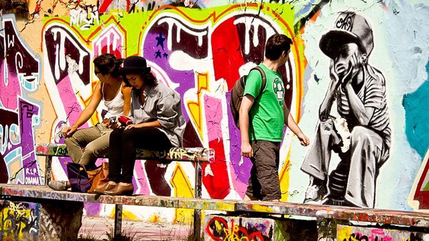 Jóvenes junto a muralescallejeros en el distrito de Friedrichshain, en Berlín. VISITBERLIN