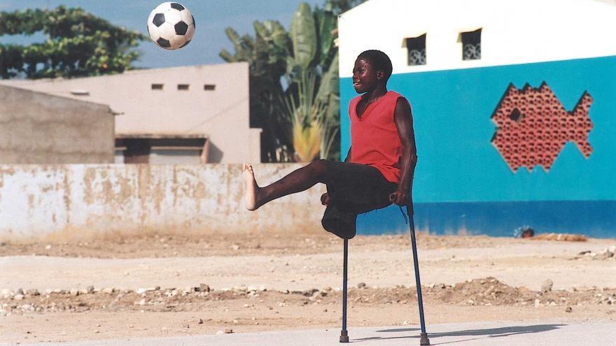 Un niño que perdió una pierna por un accidente con una mina en Angola se prepara para golpear el balón / Fotografía: Handicap International
