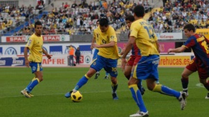 Jorge Larena conduce el balón ante la mirada de Aythami y Jonathan Viera. (ACFI PRESS)