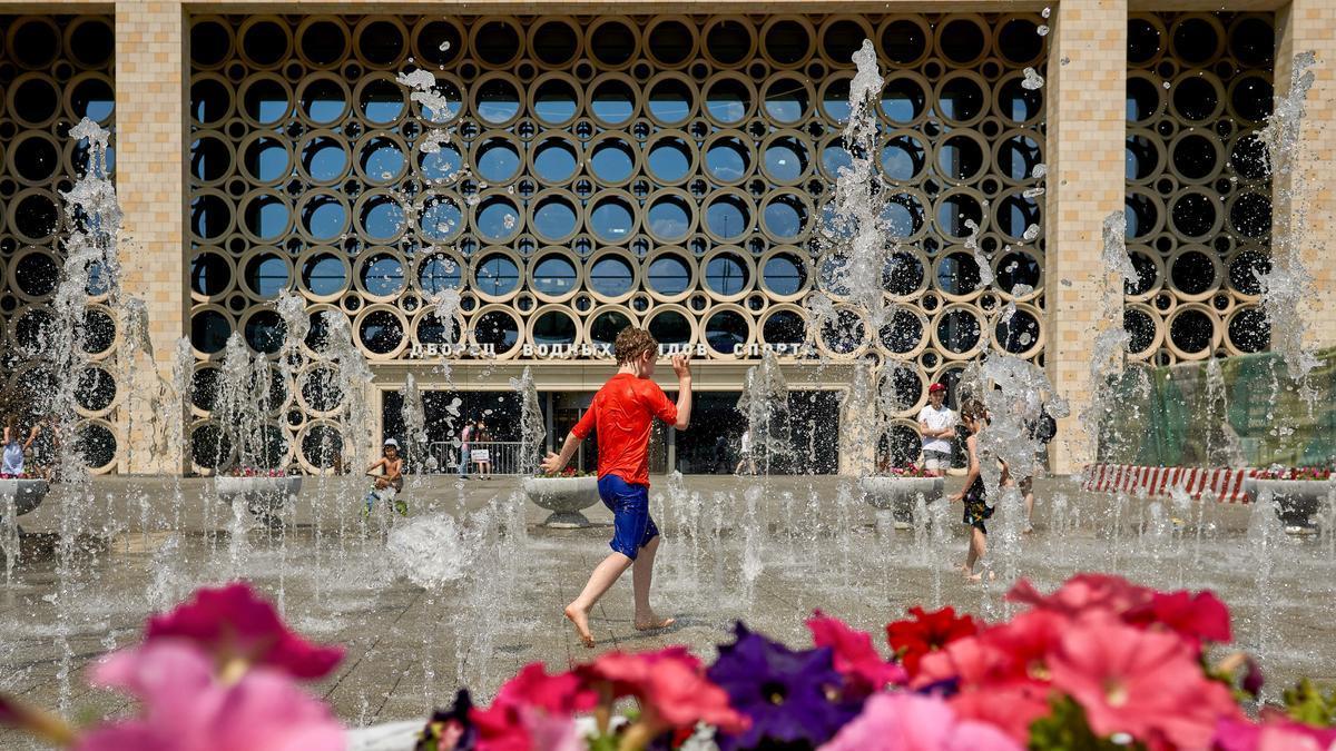 Niños se bañan en una fuente durante una ola de calor en Moscú.