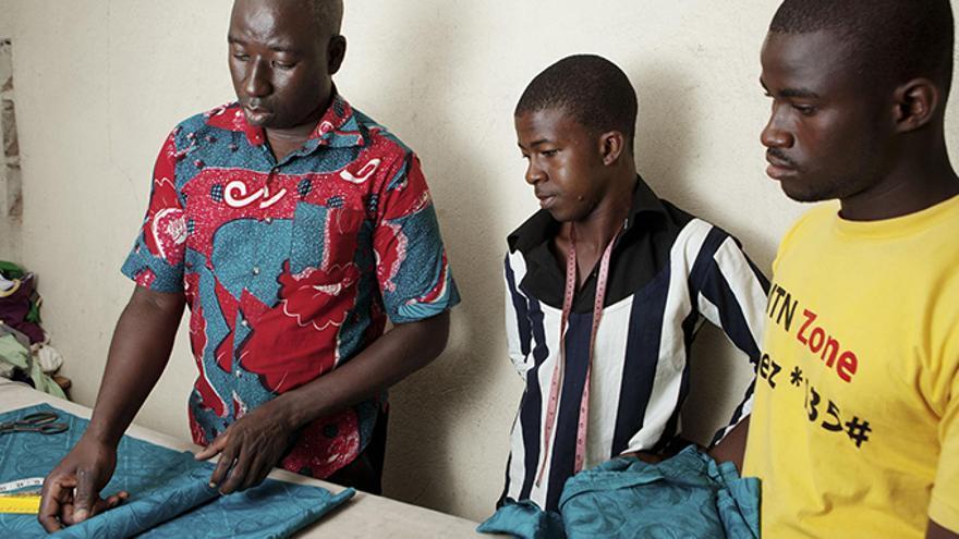 Ernest Kaboré (izq) con dos aprendices de su taller. / Alex Llopis