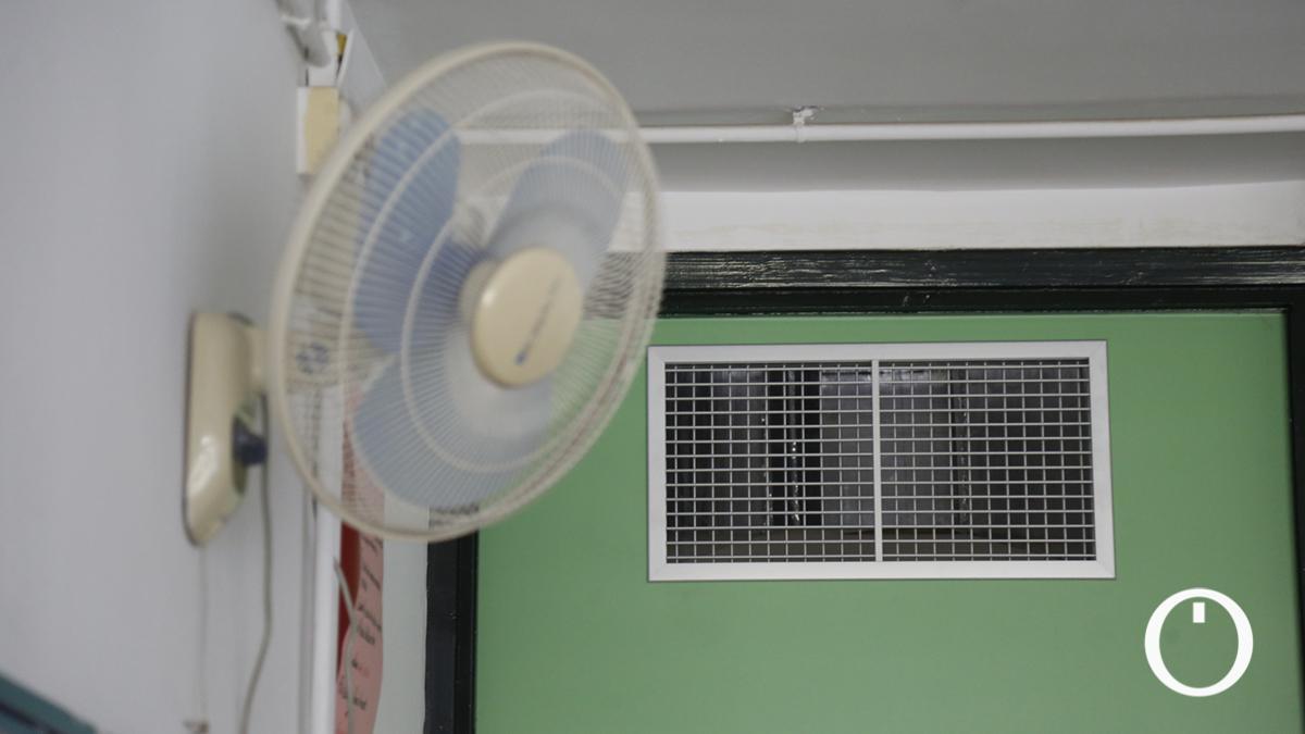 Un ventilador junto al conducto de la climatización que no se puede usar en el colegio Hernán Ruiz