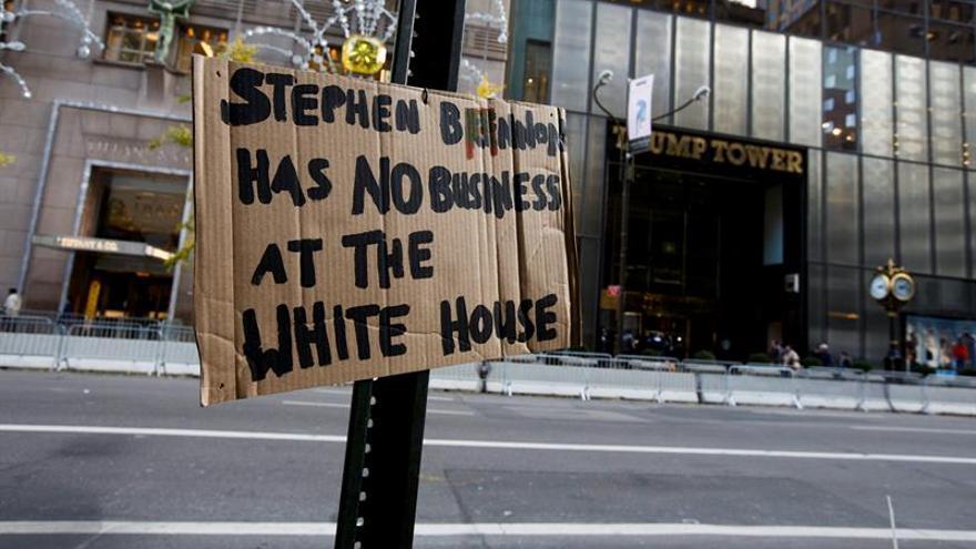 """Un cartel en el que se lee """"Stephen Bannon no debe estar en la Casa Blanca"""" cerca al edificio Torre Trump"""