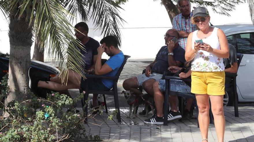 Varias personas desalojadas de sus casas por el incendio de Gran Canaria a las puertas del polideportivo municipal de Agaete este lunes donde han sido alojados desde la pasada noche. EFE/Elvira Urquijo A.