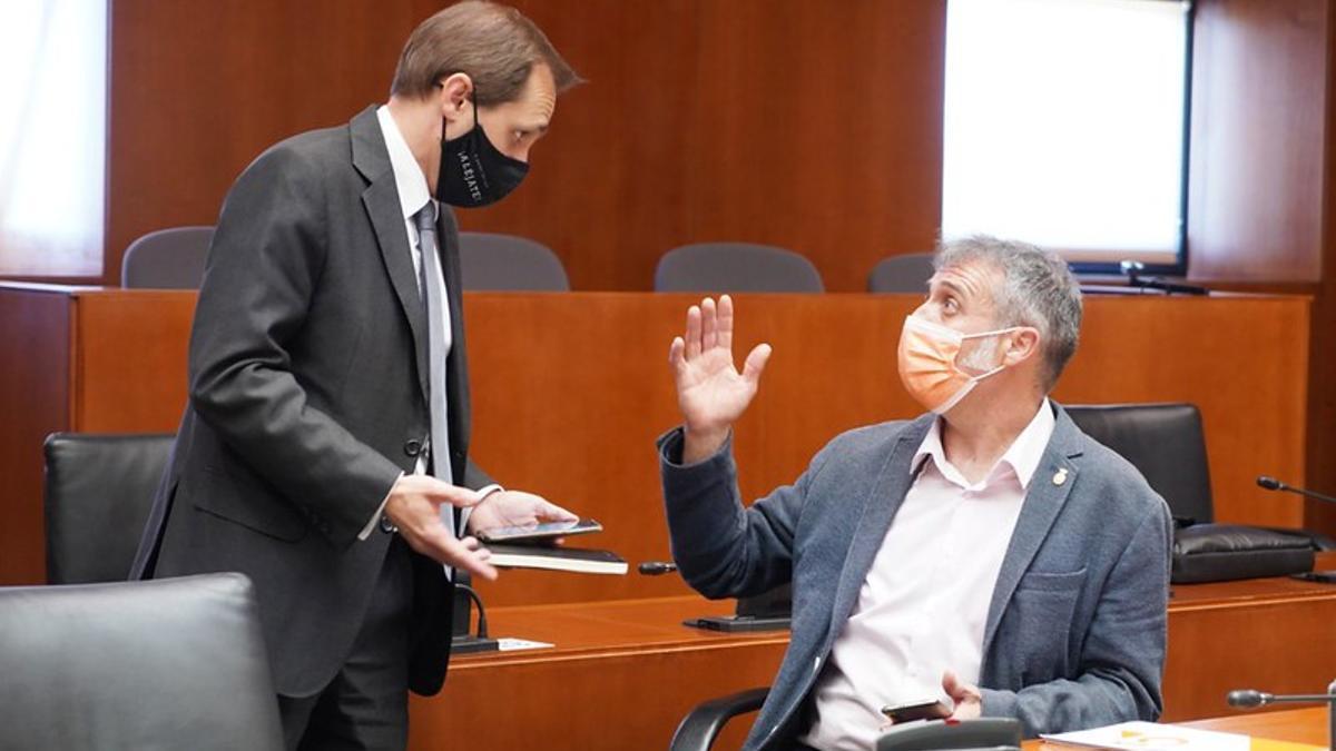 Domínguez, sentado, conversa con su compañero de partido, Carlos Trullén
