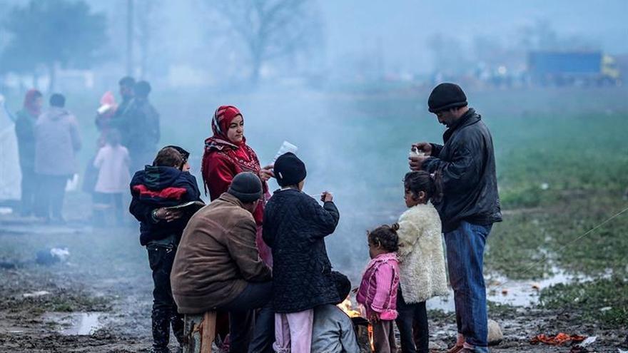 Una familia de refugiados intenta calentarse en un campamento cerca de Idomeni, en la frontera entre Grecia y Macedonia, el pasado 10 de marzo.