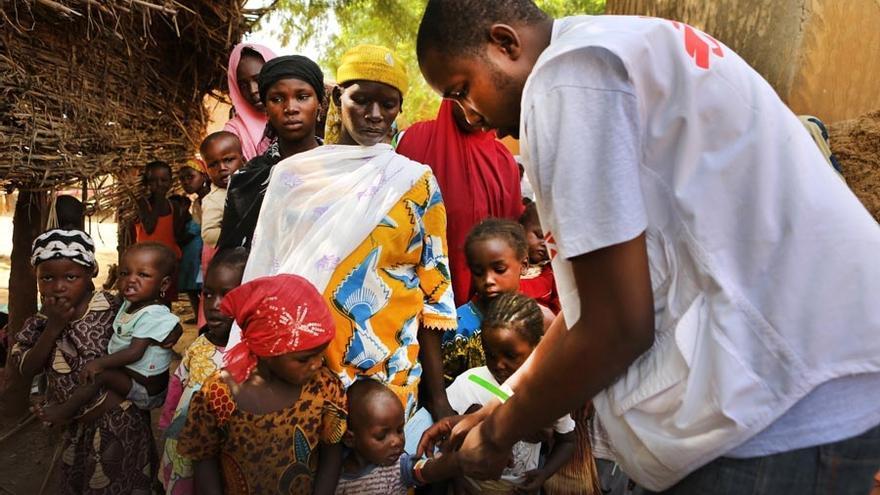 Los agentes comunitarios trabajan para lograr que el máximo número de niños sean atendidos en los puntos donde los equipos de MSF están proporcionando quimioprevención de la malaria. Las autoridades locales también participan en esta tarea de sensibilización, animando a las madres a acercarse con sus hijos. En primer lugar se revisa el estado nutricional de los niños, gracias al brazalete MUAC (de medición del perímetro mesobraquial), que permite evaluar rápidamente y de forma aproximada el estado nutricional del niño. Desde primeras horas, hay largas colas. Esta es en el pueblo de Tounfafi. / Fotografía: MSF