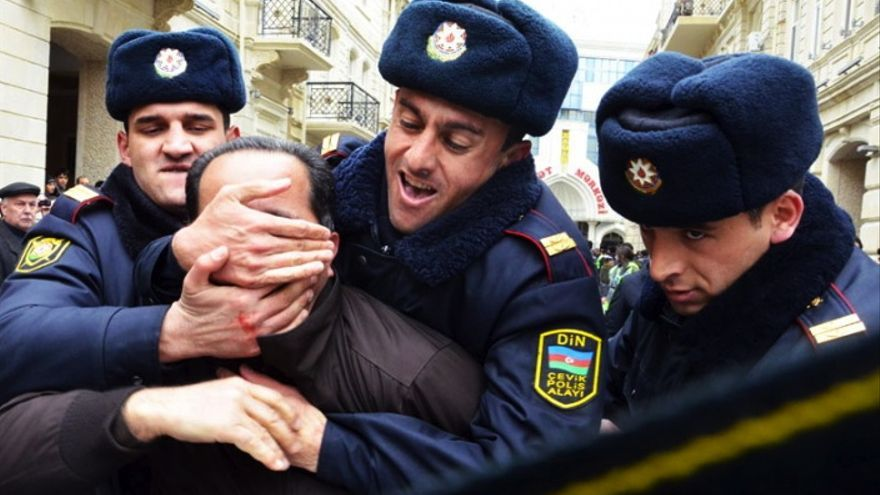 Tres policías agarran a un activista político durante una protesta en Bakú, Azerbaiyán, marzo de 2011 © IRFS