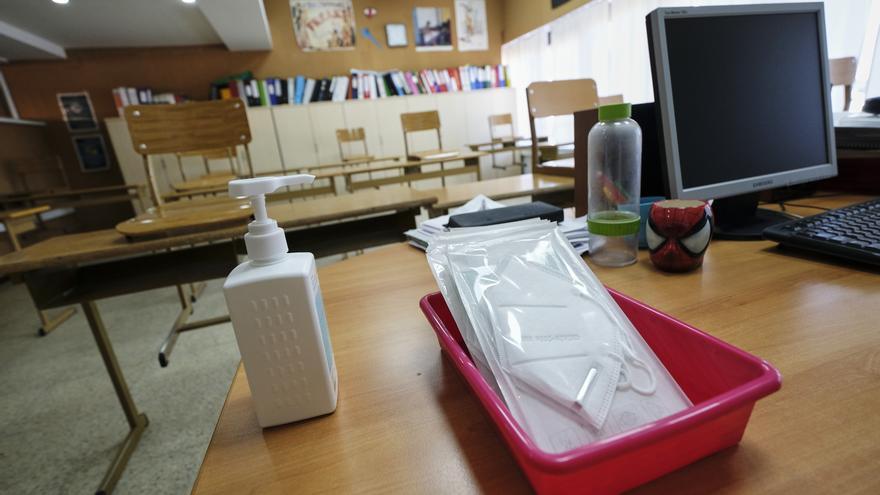 Mascarillas y gel desinfectante en la mesa de un profesor.