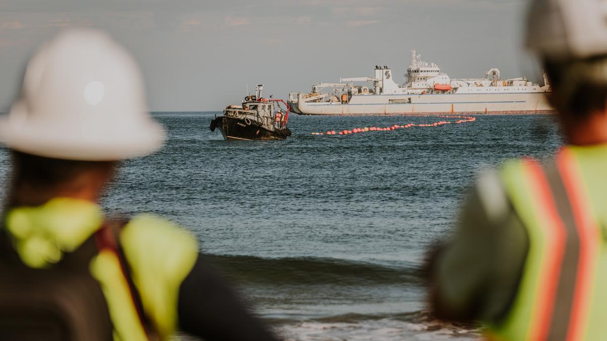 Operarios observan la última etapa del anclaje del cable en Sopelana, en Bizkaia.