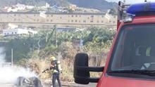 Un bombero apaga el fuego registrado en la mañana de este sábado en un contenedor de basura situado en el barrio de Mirca.