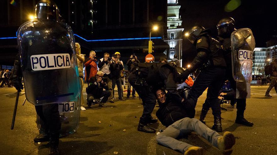 La policía arrasta por el suelo a uno de los detenidos tras los disturbios de anoche en Madrid. /Javi Julio