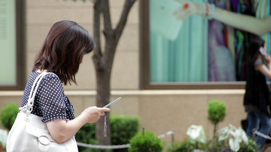 Una mujer sostiene un teléfono móvil, en una imagen de archivo