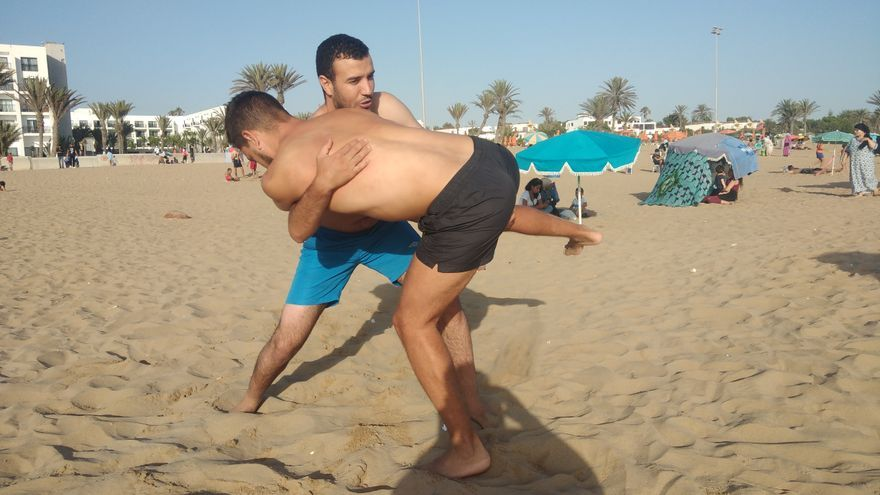 Los jóvenes practicando las luchadas del norte de África.