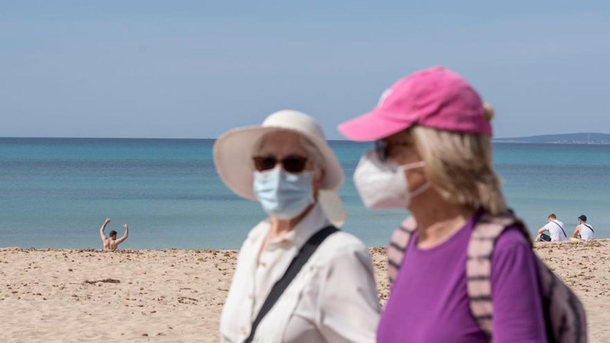 Dos mujeres con mascarilla en la playa