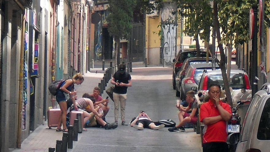 Viajeros esperando a las puertas de un edificio de viviendas turísticas sin licencia en la calle Minas   JUAN CARLOS GONZÁLEZ