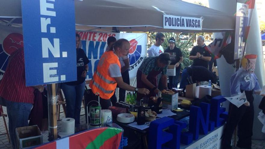 Miembros del sindicato Erne preparan pintxos de 'txorizo' y colocan las botellas de sidra en la protesta frente al BEC de Barakaldo.