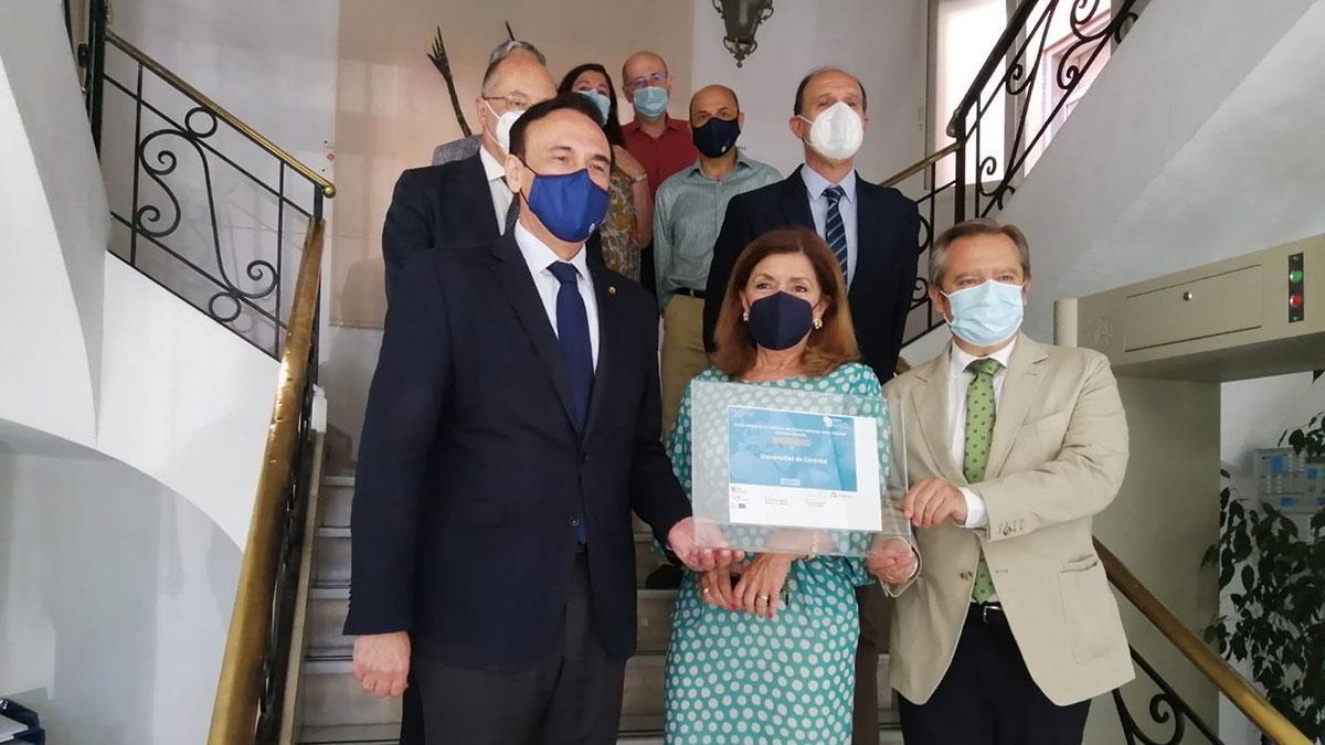 La delegada de Salud y Familias, María Jesús Botella (centro), entrega al rector de la UCO, José Carlos Gómez Villamandos (izda.), el certificado de adhesión a la Red Andaluza de Servicios Sanitarios y Espacios Libres de Humo (Rasselh).