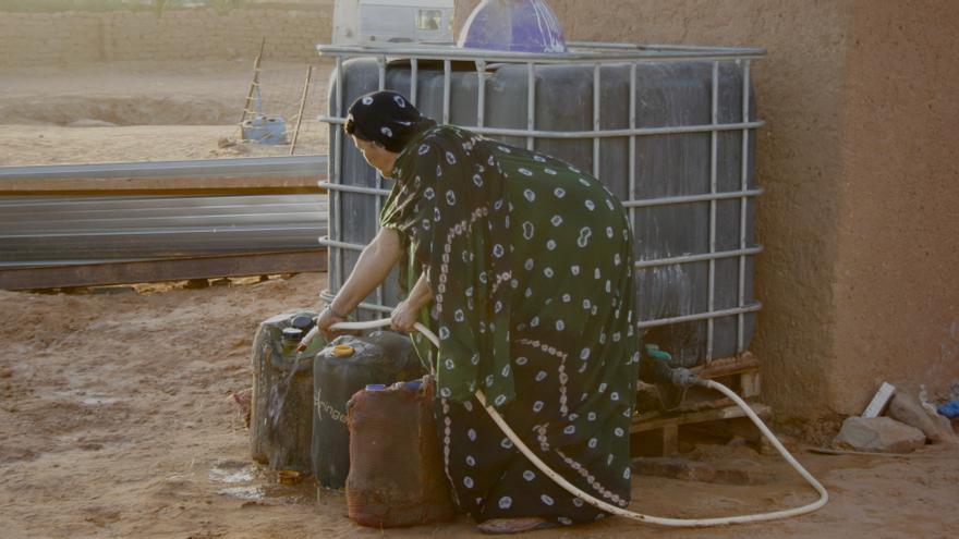 Balla distribuye el agua del tanque semanal en diferentes garrafas. Campamento de refugiados de Dajla. / G. S.