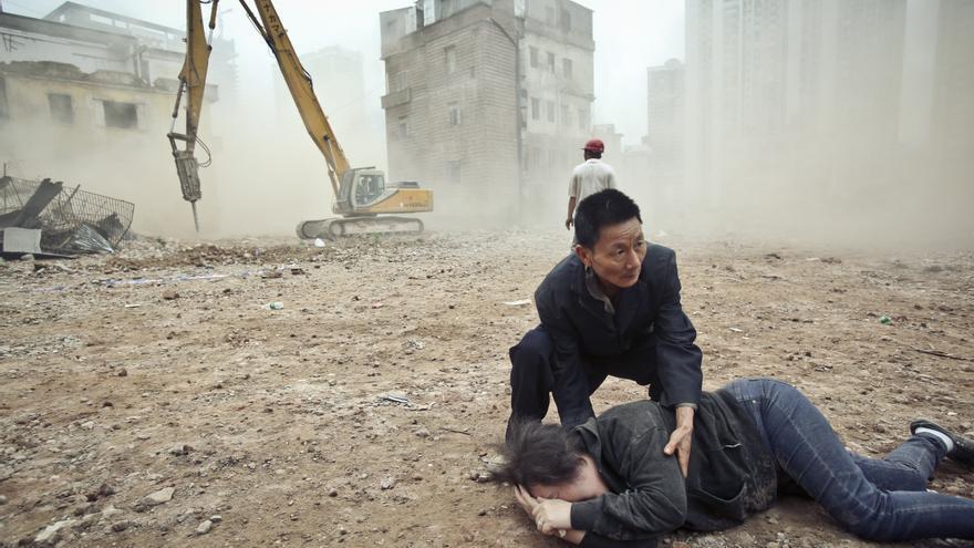 """MARZO. Las grúas continúan su trabajo de demolición mientras una mujer se derrumba en el suelo llorando. Le aseguraron que su casa no estaría dentro de los 4 edificios (que ocupan un área total de 326 metros cuadrados) derribados en Yangji, en la provincia china de Guangdong. Los desalojos forzosos y violentos van en aumento en China: de los 40 que Amnistía Internacional ha examinado detenidamente en el marco de la investigación para el informe """"Standing their ground"""", 9 dieron lugar a muertes de personas que protestaban o se oponían a ellos. #StopDesalojosForzosos // ©  AP Photo/Imagine China"""