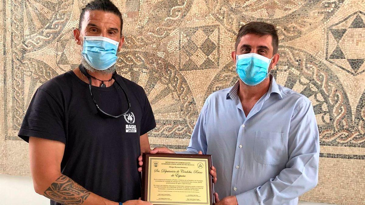 Ramón Hernández (dcha.), recibe la placa de reconocimiento de manos de Antonio García, en representación de Bomberos Unidos Sin Fronteras.