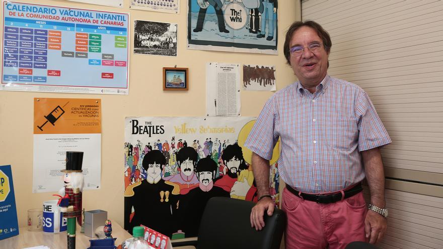 Amós García Rojas en su despacho en el Servicio Canario de Salud, delante del póster de uno de sus grupos de cabecera