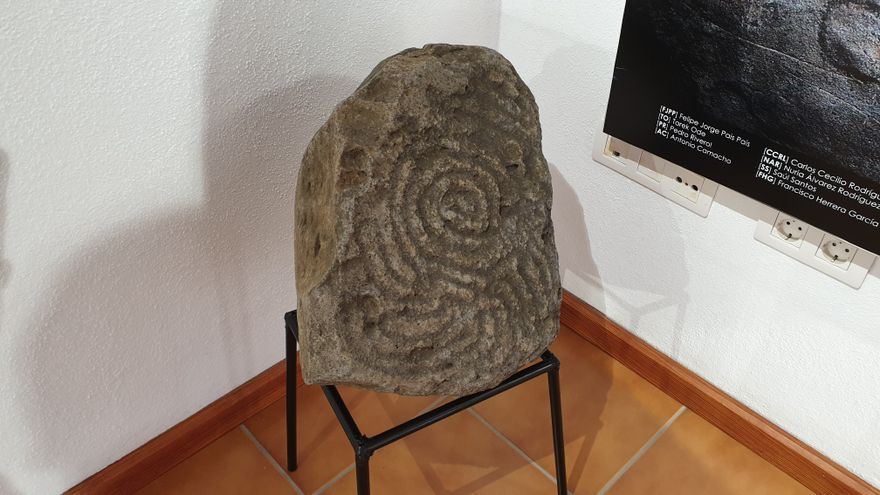 Piedra con inscripciones aborígenes expuesta en el centro.
