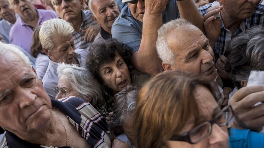 Jubilados intentan coger número para entrar en la sucursal para sacar hasta 120 euros en efectivo de sus pensiones.  / AP Photo