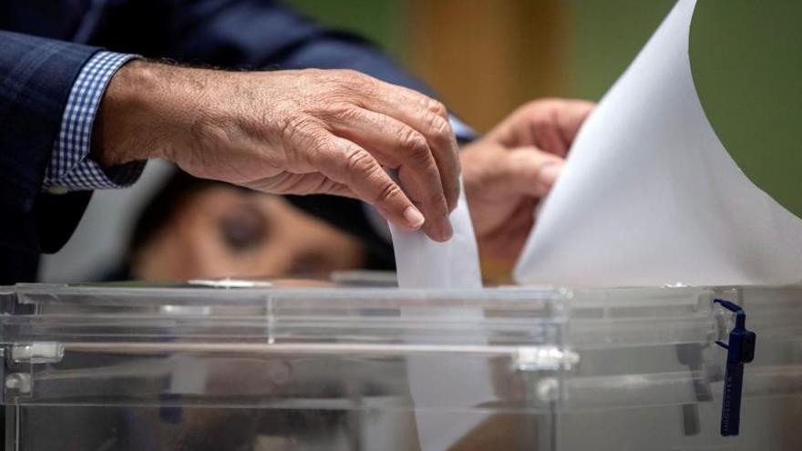 El presidente de una mesa electoral introduce un voto en una urna, hoy en el Colegio San José de Lorca.