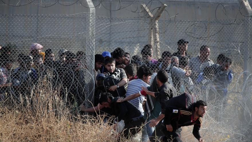 Refugiados sirios cruzan la valla que separa su país de Turquía, en la zona fronteriza de Akcakale (Siria). Los combates entre los soldados kurdos y las milias del Estado Islámico en la ciudad próxima de Tal Abyad ha provocado un aumento de las familias que buscan refugio en el país vecino. / (AP Photo/Lefteris Pitarakis).