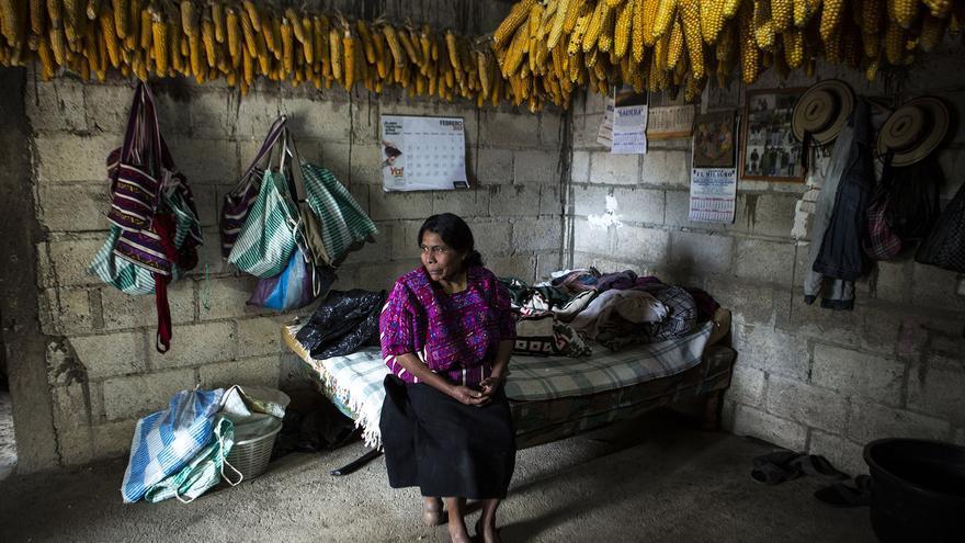 Juana posa para un retrato sentada en la cama de su casa en San Juan Atitán